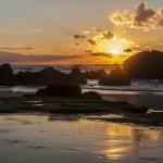 Se pone el sol entre las rocas de la Playa de Valdearenas