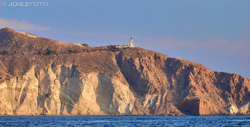 Faro de Akrotiri en la puesta de sol desde la caldera